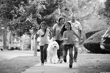 Family of four running with their dog on the sidewalk