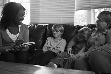 Social working sitting on couch with mom and two kids