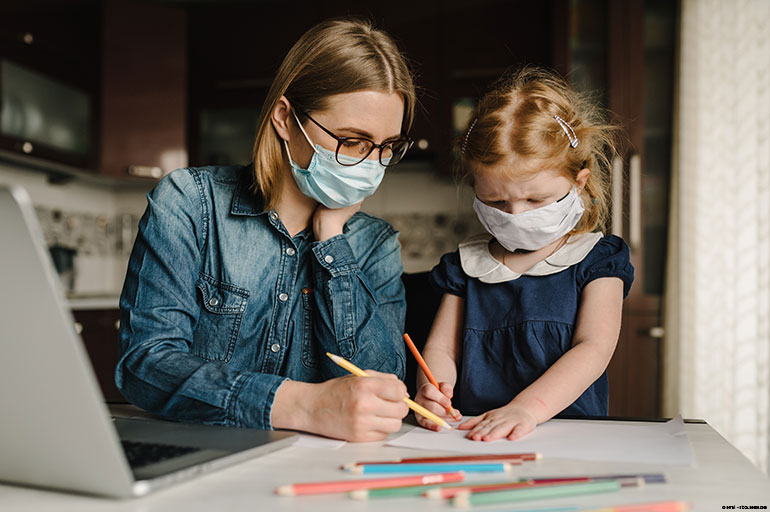 Adult and child doing school work wearing face masks