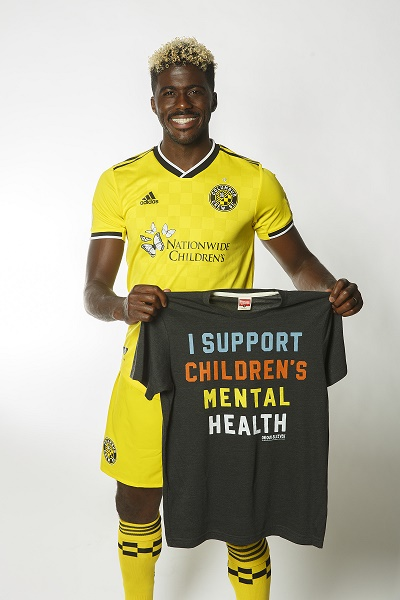 "Columbus Crew player holding up a ""I Support Children's Mental Health"" Homage Tshirt"