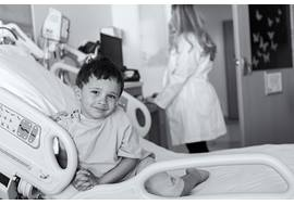 Young boy smiling in hospital bed with physician in background